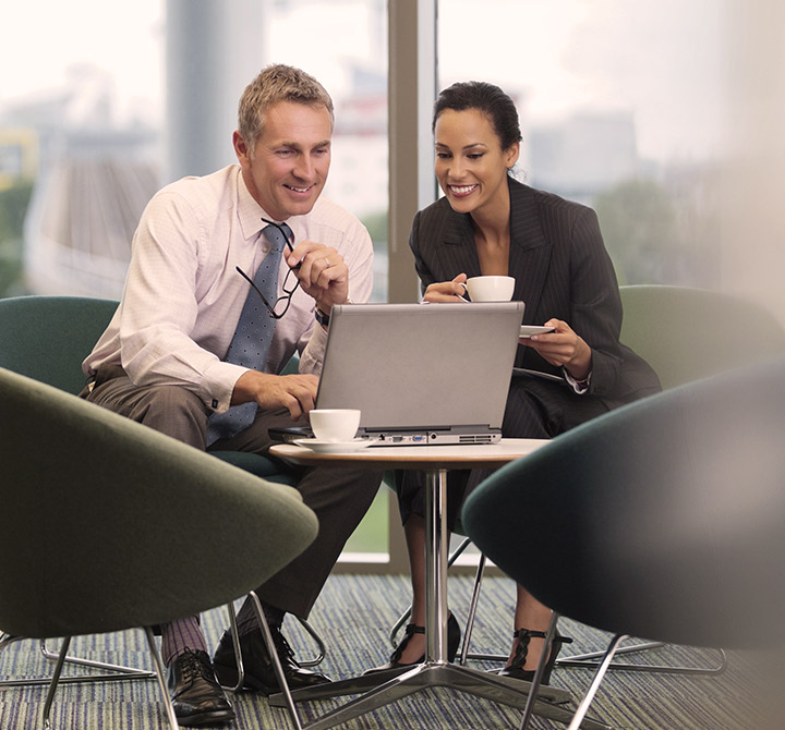 Man and woman in office setting seated together with coffee looking at a laptop.