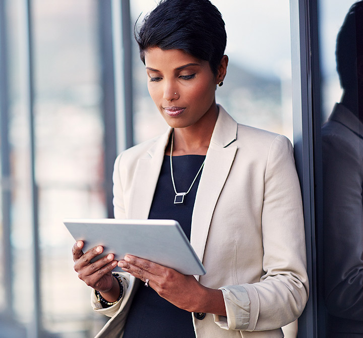 A business woman leaning against a window looking at a tablet.