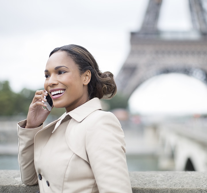 Woman talking on smartphone with Eiffel Tower in the background.