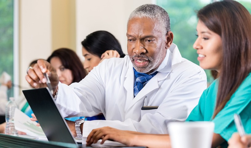 Senior adult African American doctor and professor is assisting a young adult Hispanic female nursing or medical student in class. Doctor is pointing to laptop computer screen while nursing student types. Other healthcare students are studying around them.