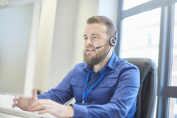a call centre phone operative in his mid 30s chats on the phone at his desk . He looks in complete control of the situation and smiles through the mass of fur .